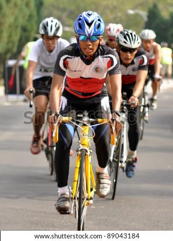 KUALA LUMPUR - SEPT 24: An unidentified participant cycles after run 5km at Malakoff University Duathlon Series 2011, on September 24, 2011 in Kuala Lumpur, Malaysia - stock photo