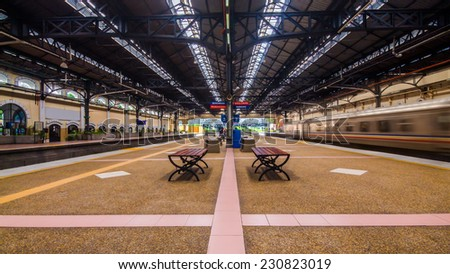 Kuala Lumpur train station with empty seat and a train passing by with a motion blur. - stock photo