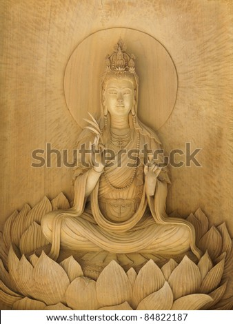 Kuan Yin image of buddha , Wood carving in a thai temple. - stock photo