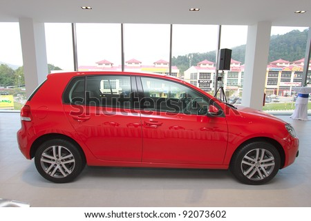 KUANTAN,MALAYSIA-JAN.4: Side view of red Golf at the launching of Volkswagen Showroom on January 4th 2012 in Kuantan, Pahang, Malaysia. Official opening celebration on 7th and 8th January 2012. - stock photo