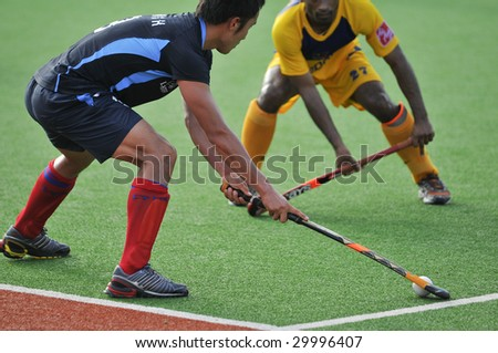 KUANTAN, MALAYSIA - MAY 9 : Korean Yoon Sung Hoon (L) controls the ball away from Malaysian player at 8th AirAsia Men's Asia Cup 2009 hockey tournament May 9, 2009 in Kuantan, Pahang, Malaysia.