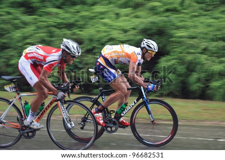 KUANTAN-MARCH 2: Hao Liu (MAX Success Sports) & Wijaya Endra (Indonesia Team) in action during Stage 8 of the le Tour de Langkawi from Bentong to Kuantan on March 2, 2012 in Kuantan, Pahang, Malaysia. - stock photo