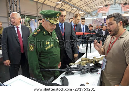 KUBINKA, MOSCOW OBLAST, RUSSIA - JUN 16, 2015: The Minister of Defense Sergey Shoygu examines the weapon on the stand of the concern Kalashnikov at the International military-technical forum ARMY-2015 - stock photo