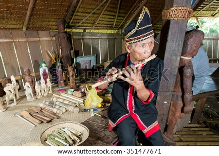 KUCHING, MALAYSIA - December 14, 2015 :An unknown man from the Bidayu tribe playing flute, a traditional musical instrument at Sarawak Culture Village. - stock photo