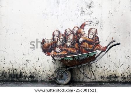 KUCHING, MALAYSIA - FEBRUARY 21, 2015 : Street art of Orang Utans in a wheelbarrow by Lithuanian artist Ernest Zacharevic. - stock photo