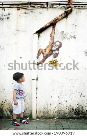 KUCHING, MALAYSIA - MAY 1: Young boy looking at wall mural of an orangutan painted by Lithuanian street artist Ernest Zacharevic along Jalan Power, Kuching, Sarawak on April 27, 2014.