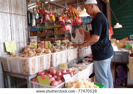 KUCHING - MAY 13: An unidentified man packs the fruits at his grocery shop in town, May 13, 2011 in Kuching, Borneo Island. Most of the shops cater to the town-folks and a growing number of tourists.