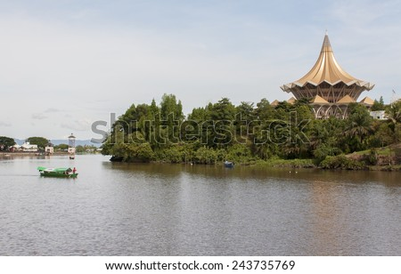KUCHING, SARAWAK - SEPTEMBER 24: Traditional river boat transporting people across Sarawak River with State Legislative Assembly as the background on September 24, 2010 in Kuching, Sarawak, Malaysia