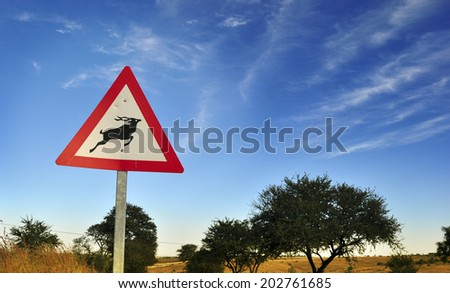 Kudu antelope crossing traffic sign in South Africa against blue sky - stock photo