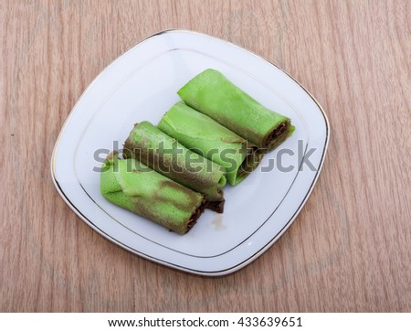 Kueh ketayap (kueh dadar) is one of traditional food for malays in Malaysia. Juicy palm sugar flavored shredded coconut fillings that is wrapped in a piece of screw-pine flavored green crepe. - stock photo