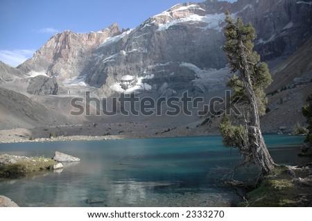 Kulikalon wall and Adamtash peak by cool lake. Tajikistan. - stock photo
