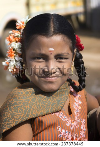 KUMBAKONAM, INDIA - OCTOBER 11, 2013: A young unidentified  Hindu schoolgirl with flowers in her black hair faintly smiles into the camera. In the close-up, her orange shirt and matching scarf accent her face.