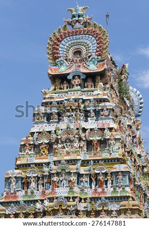 KUMBAKONAM, INDIA - OCTOBER 12, 2013: Mahalingeswarar Temple. Tens of pastel colored statues of deities and others. The central statue of Lord Shiva with a few disciples and his foot on the dwarf.