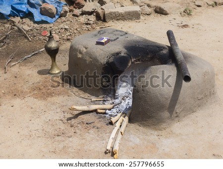 KUMBAKONAM, INDIA - OCTOBER 11, 2013: Mud kitchen stove in village outside home. Remnants of firewood, ashes and matches. The pot will be set on top of the round opening. - stock photo