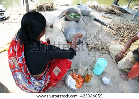 KUMROKHALI, INDIA - JANUARY 17: Traditional way of making food on open fire in old kitchen in a village, Kumrokhali, West Bengal, India January 17, 2009. - stock photo