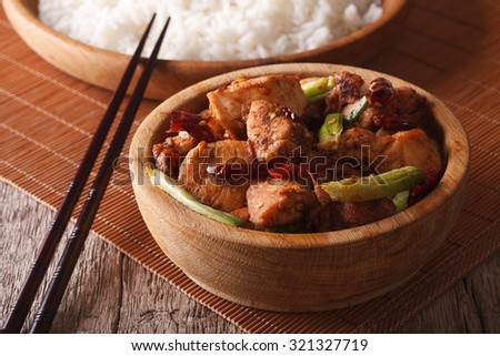 Kung pao chicken fillets in a bowl close up and rice. Horizontal
