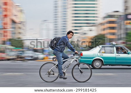 KUNMING-JULY 5, 2014. Man on a white UCC bicycle. UCC, founded in 1990 is a Chinese brand located in Guangzhou, manufacturing high class bicycles. Its annual sales volume meets 450 million RMB.   - stock photo