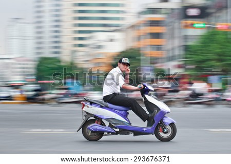 KUNMING-JULY 5, 2014. Man on an electric bike. An estimated 200 million Chinese now use e-bikes, 1,000-fold increase from 15 years ago. About 90 percent of world's e-bikes were sold in China in 2012. - stock photo