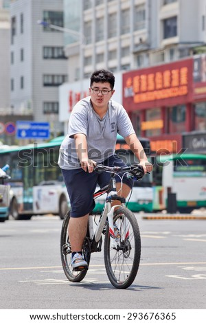 KUNMING-JULY 5, 2014. Overweight boy on mountain bike. China's obesity rate has skyrocketed over last three decades, resulting in 46 million obese Chinese adults and 300 million who are overweight. - stock photo
