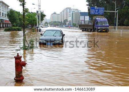 KUNMING - JULY 19: Unidentified people and vehicles caught in the flooded streets after intense rain storms, Kunming China July 19, 2013