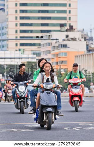 KUNMING-JUNE 30, 2014. Girls on an e-bike. An estimated 200 million Chinese now use e-bikes, 1,000-fold increase from 15 years ago. About 90 percent of world's e-bikes were sold in China in 2012. - stock photo
