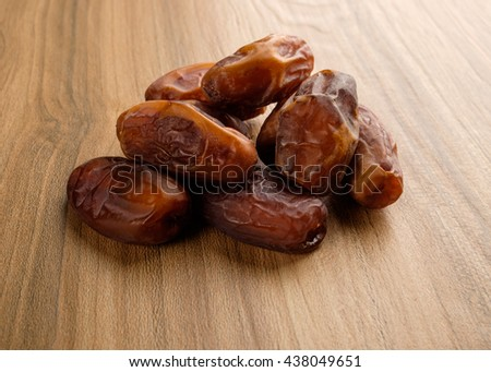 Kurma or dried dates fruit on wooden background. Dates are popular as food supplement during Ramadan among Muslims during iftar. - stock photo