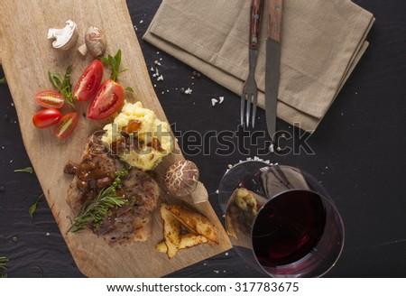 Kurobuta steak, Japanese Kurobuta pork steak with brown sauce decorated with herbs and vegetable on wood block - stock photo