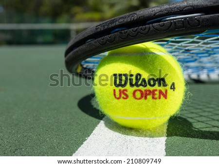 KURUMBA, MALDIVES - JUNE 21 , 2014: Photo of a brand Wilson tennis balls on clay court.  Wilson -  American company of sporting goods. Wilson tennis balls are  official balls of  Davis Cup, Fed Cup. - stock photo