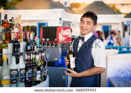 KUSADASI/TURKEY - JUNE 2, 2013: Smiling turkish barmen with a bottle of red wine in the outdoor bar.