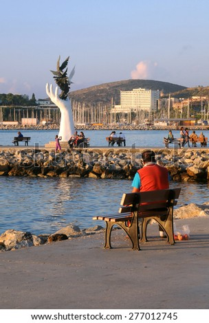 KUSADASI, TURKEY - OCTOBER 4, 2009: People relax in the port at sunset  - stock photo