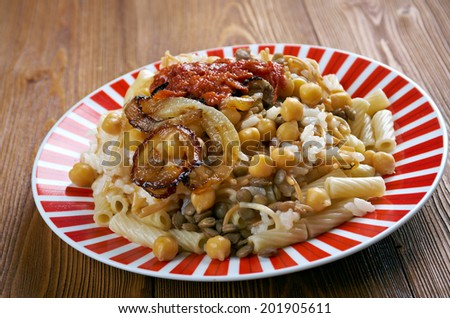 Kushari - is an Egyptian dish of rice, macaroni and lentils mixed together, topped with a tomato-vinegar sauce - stock photo