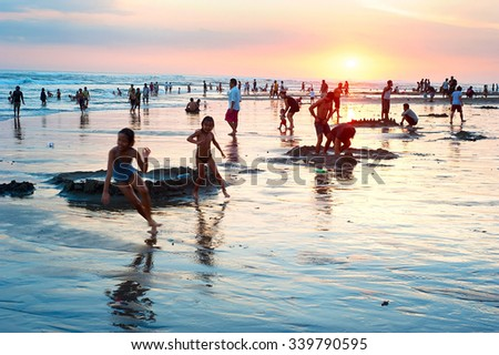 KUTA, BALI ISLAND, INDONESIA - MARCH 17, 2013: Local people resting at the ocean beach on Bali island. With a population of currently 4.22 million, island is home to most of Indonesia's Hindu minority