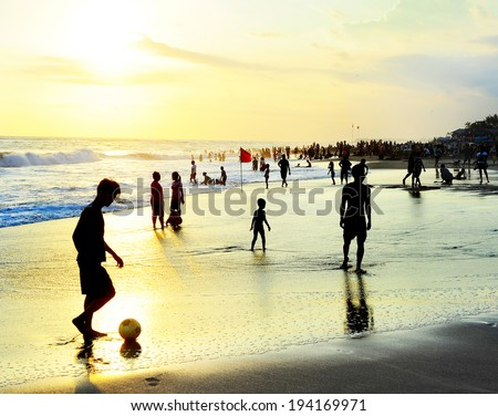 KUTA, INDONESIA - MAY 05,2013: Unidetified people plaing soccer on the beach in Kuta, Indonesia. Football is the most popular sport in Indonesia. The Indonesian football league started around 1930  - stock photo