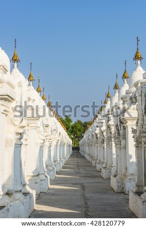 Kuthodaw Pagoda contains the worlds biggest book. There are 729 white stupas with caves with a marble slab inside - page with buddhist inscription. Mandalay, Myanmar - stock photo