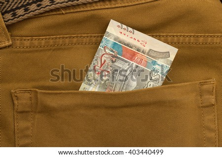Kuwait Banknote in back pocket of blue jeanse - stock photo