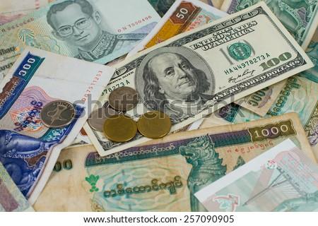 Kyat,  yuan, baht, coins and hundred-dollar bill on the heap. - stock photo