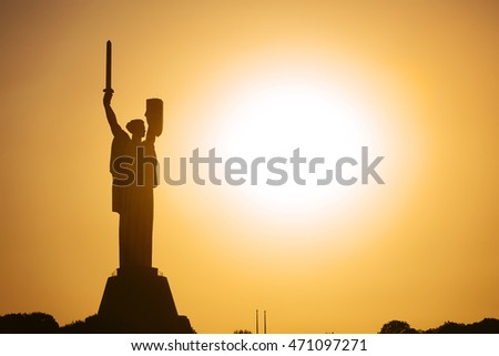 Kyiv - August 2016: Motherland monument with sword and shield with former USSR state emblem opened in 1981 at sunset with sun, August 06, 2016, Kyiv, Ukraine