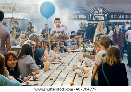 KYIV, UKRAINE - APR 17: Big table of outdoor restaurant with eating and drinking people during popular Street Food Festival on April 17, 2016. Kiev is the 8th most populous city in Europe. - stock photo
