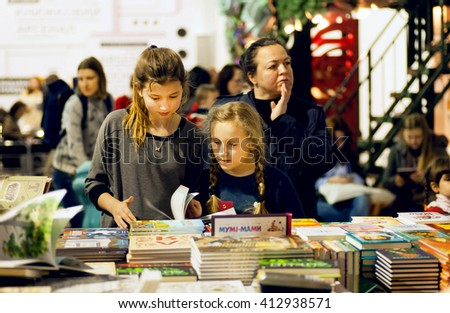 KYIV, UKRAINE - APR 21: Unidentified girls reading books at children booth of the 6th Festival BOOK ARSENAL on April 21, 2016. Guests of the fair were writers Lars Svendsen, Vigdis Hjorth, Etgar Keret - stock photo