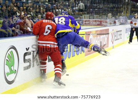 KYIV, UKRAINE - APRIL 20: Michal Kotlorz of Poland (L) fights for a puck with Dmytro Isayenko of Ukraine during their IIHF Ice-hockey World Championship DIV I game on April 20, 2011 in Kyiv, Ukraine - stock photo