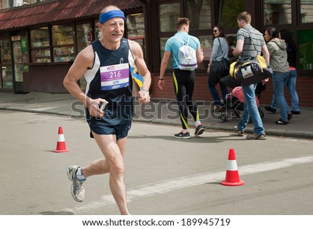 KYIV, UKRAINE - APRIL 28: Senior contender runs smiling during 5-th Wizz Air Kyiv City Marathon, a competition run of 5, 10 and 42 km held in the old city center on April 28, 2013 in Kyiv, Ukraine.  - stock photo
