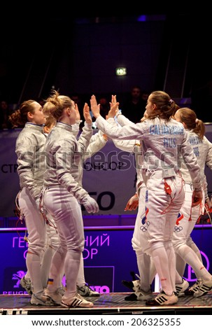 KYIV, UKRAINE - APRIL 13, 2012: Ukrainian and Russian fencers cheer each other up before Womens Sabre final match of World Fencing Championships - stock photo