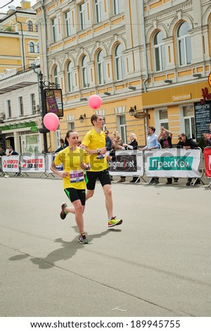 KYIV, UKRAINE - APRIL 28: Young couple runs with red balloons during 5-th Wizz Air Kyiv City Marathon, a competition run of 42 km held in the old city center on April 28, 2013 in Kyiv, Ukraine.  - stock photo