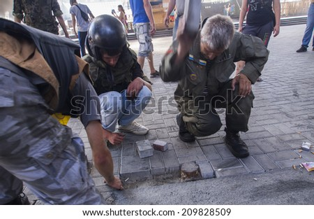 KYIV, UKRAINE - Aug 7, 2014: Activists pick out paving tiles. -- Activists and police have clashed in the Ukrainian capital's center after communal workers tried to dismantle the camp.