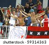 KYIV, UKRAINE - AUGUST 17: AFC Ajax fans celebrate after scoring against FC Dynamo Kiev during their UEFA Champions League play-off game on August 17, 2010 in Kyiv, Ukraine - stock photo