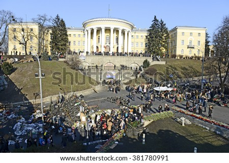 KYIV, UKRAINE-CIRCA MARCH, 2014: Place of mass shooting of protesters at 18-20 February 2014 on Institutska street. Peoples near barricades, Palace of Art, symbolic memorial from flowers and tyres