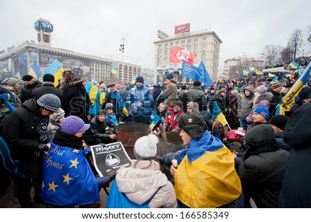 KYIV, UKRAINE - DEC 8: Many people warm themselves by the fire on the cold occupying Maidan square during two weeks anti-government protest on December 8, 2013, in Kiev, Ukraine. - stock photo