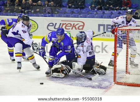 KYIV, UKRAINE - FEBRUARY 9: Denys Zabludovskiy of Ukraine (in Blue) fights for a puck with Romanian players during their Euro Hockey Challenge game on February 9, 2012 in Kyiv, Ukraine - stock photo