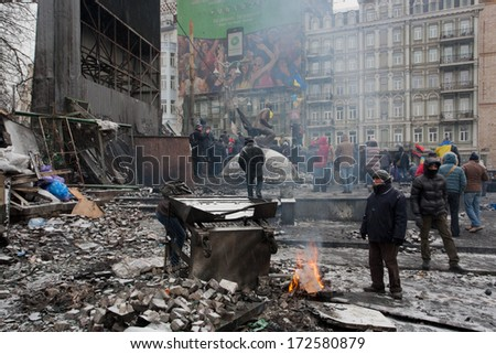 KYIV, UKRAINE - JAN 21: Active people burn fire past barricades after night fights on the destroyed winter street during anti-government protest Euromaidan on January 21, 2014, in Kiev, Ukraine.   - stock photo