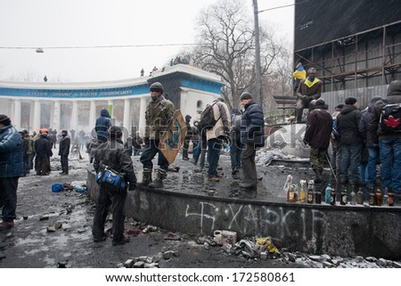 KYIV, UKRAINE - JAN 21: Activists of the riot in uniform wait for the fight with police in the burned square during anti-government revolution Euromaidan on January 21, 2014, in Kiev, Ukraine.   - stock photo